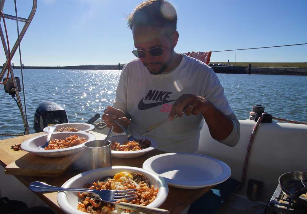 Mann isst Krabbenbrot mit Spiegelei auf Segelboot