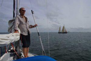 Mann steht am Mast vom Segelboot auf der Nordsee und schaut in die Ferne
