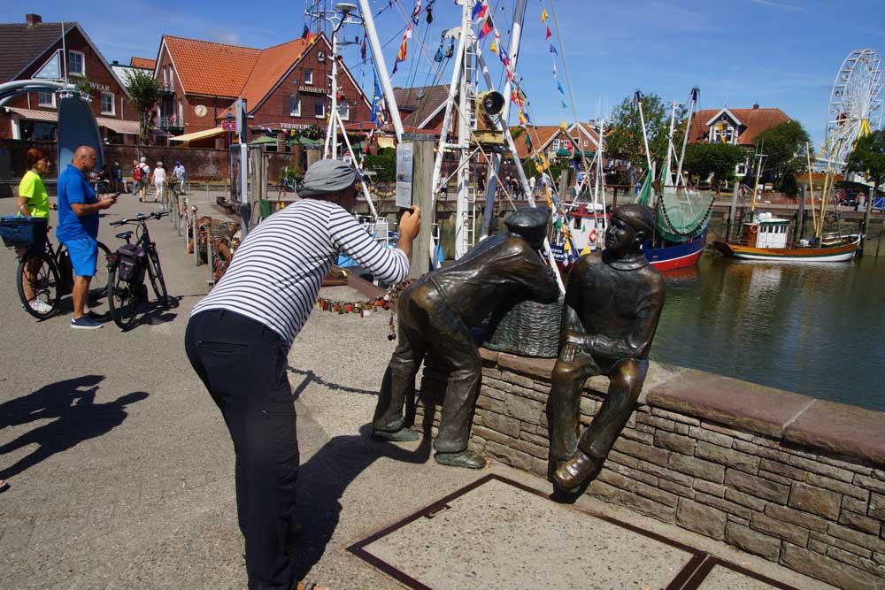 Mann fotografiert Figuren im Hafen von Neuharlingersiel