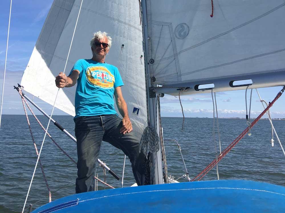 Mann steht am Mast vom Segelboot auf der Nordsee